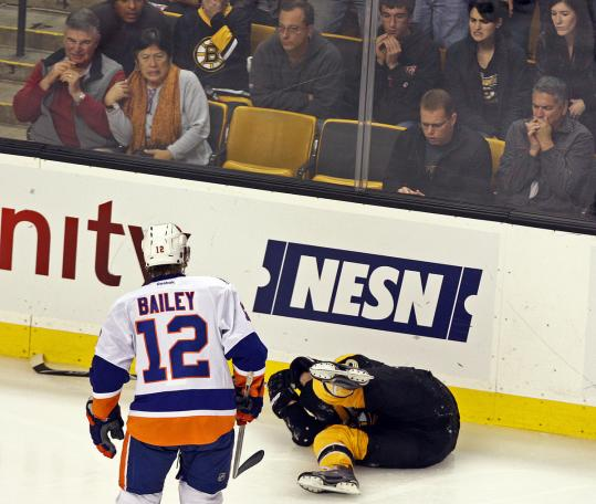 With the Islanders' Josh Bailey (12) looking on, Daniel Paille falls in a heap after taking a puck to the face.