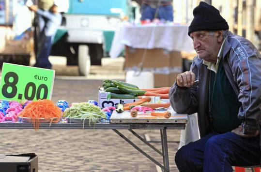 A man sold vegetable peelers at a street market yesterday in Rome, where the European Commission has started a verification mission to check on Italy's budget efforts.