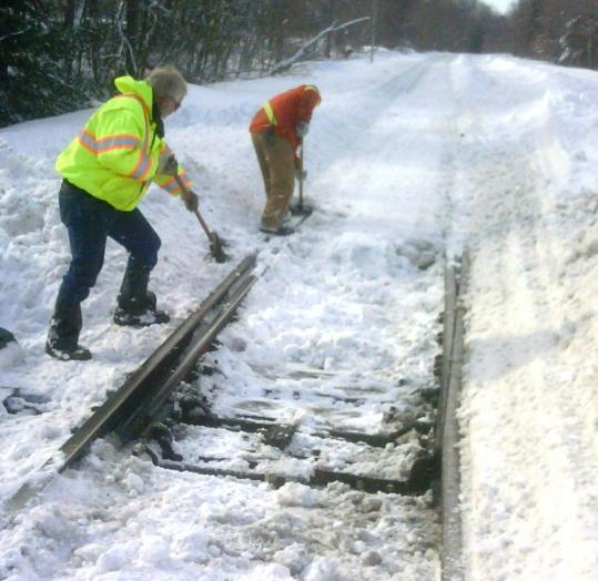 Workers cleared snow from the MBTA's commuter rail line in Walpole last winter.