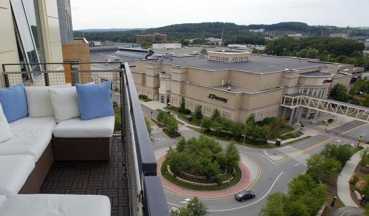 A penthouse balcony in the Nouvelle at Natick condo complex offers a sweeping view of the area, including the adjacent mall.