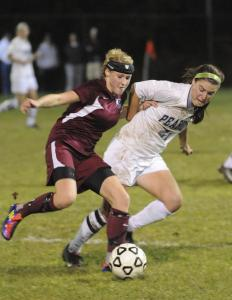 Concord-Carlisle's Andrea O'Brien (left) controls the ball as Peabody's Hayley Dowd bears down.