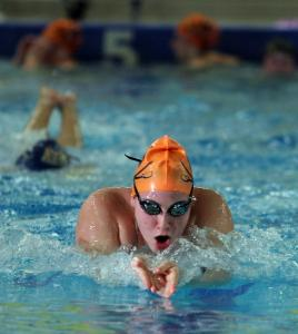 Emily Muller of the Walpole High School swim team practices at Blue Hills Regional Technical School in Canton with her team. At left, Walpole coach Cheryl Cavanaugh directs her team at the practice.