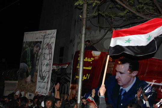 Supporters of President Bashar Assad displayed portraits of him at the entrance of the Qatari Embassy in Damascus. The Arab League is putting pressure on the dictator.