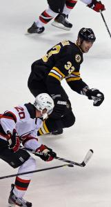 A stickless Zdeno Chara keeps the Devils' Ryan Carter (20) clearly in his sights during a rush in the second period.