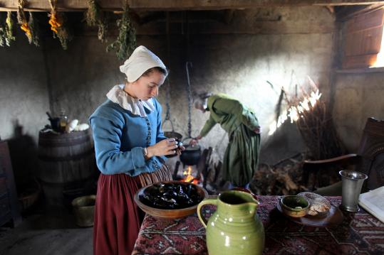 Plimoth Plantation staff portraying Lucretia Brewster and her father-in-law, William, prepare mussels and other food for a 17th-century-style meal.