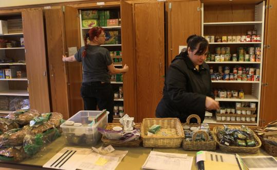Paula Torres of Brookline (right) picks out staples at the Brookline Emergency Food Pantry, where volunteers say usage has spiked in the last two years.