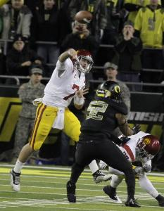 Southern Cal's Matt Barkley (7) throws on the run as tailback Curtis McNeal blocks Oregon's Dewitt Stuckey. The Trojans built a big enough lead to survive the Ducks' late rally in Oregon.