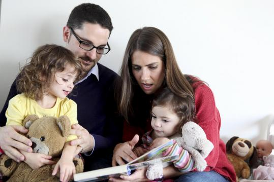 Ari and Sharon Wallach of New York read books to their twin daughters Ruby (left) and Eliana. Many parents say they want their children to be surrounded by print books and to experience turning pages as they learn about shapes, colors, and animals.