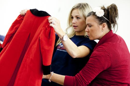 Paige Popich (left) and Rob Ninkovich&#8217;s sister Laura sorted coats at a benefit for Cradles to Crayons at Patriot Place.