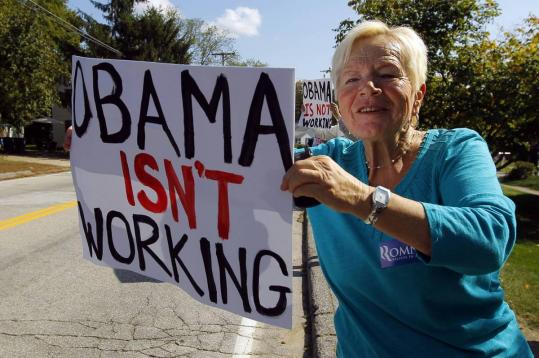 Maggie Korpi held an anti-Obama sign outside a campaign stop by Republican Mitt Romney in Goffstown, N.H., in September.