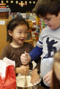 Davis Elementary students June Kim and Max Fitzgerald (above) and their classmates (top right) join forces to cook treats featuring pumpkins from the Bedford school's garden.