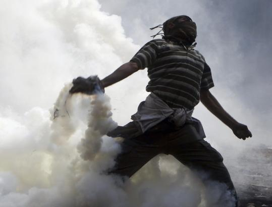 A protester throws a tear gas canister, which was earlier thrown by riot police, near Tahrir Square in Cairo Tuesday.