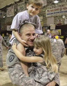 Captain Eric Folsom carries his children after returning from Iraq to Hawaii last weekend. He is part of the gradual withdrawal of US troops from Iraq.