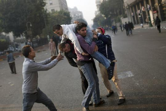 An injured protester was helped by others during clashes with Egyptian security forces in Cairo yesterday. One protester was killed when he was run over by a police vehicle.