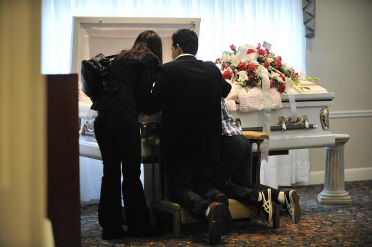 Richard Nunez, husband of Rosanna Mirielle Camilo, at her casket with two of their children, Navila (left) and Richard.