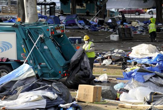 Workers cleaned up the aftermath of Occupy Los Angeles. Police raided the camp and arrested about 300 people early yesterday.