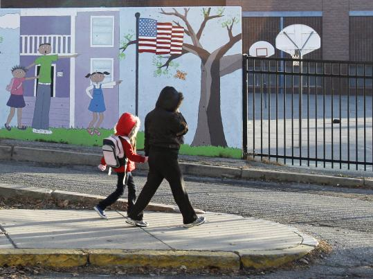 "A parent escorts her child to Arlington Elementary School in Lawrence. Mayor William Lantigua said ""the process'' failed the students."