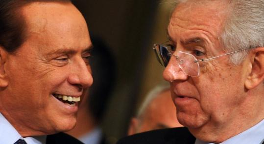 Italy's new Prime Minister Mario Monti, right, reacts to Silvio Berlusconi.