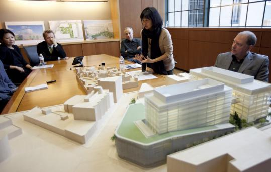 "Maya Lin (center) discussed the new Novartis AG structure using a model. Lin said of her design, ""We're trying to create something almost more campus-like in scope and feel.''"