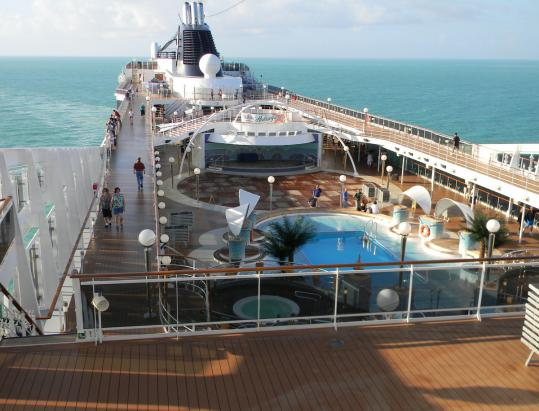Looking down on one of the 16 decks (12 for guests) on the MSC Poesia, which launched in 2008. Below, the author (rear) and yoga instructor Sherri Baptiste practice their warrior poses.