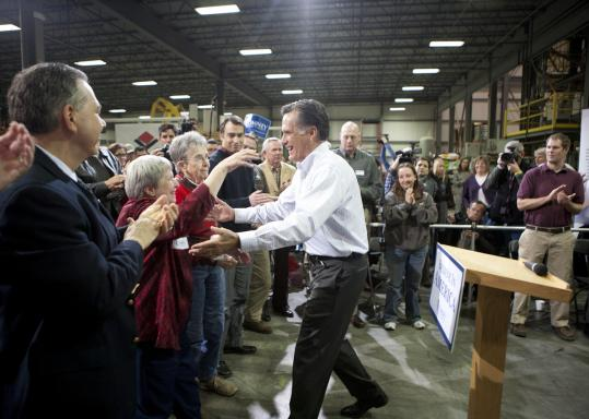 Joanie Scotter (first woman, left) greeted GOP presidential candidate Mitt Romney during a town hall event yesterday in Cedar Rapids, Iowa.