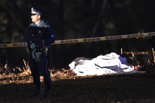 The body of John Brosnahan, a former Bedford police officer, lay covered with a sheet next to the Charles River in Brighton.