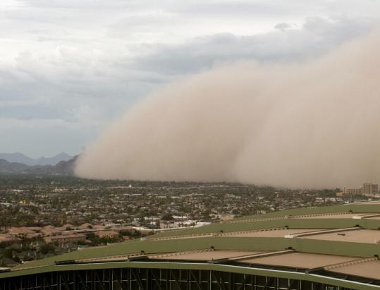 A dust storm engulfed Camelback Mountain in Phoenix in August. From off-road vehicle use to drought's impact on plants, more dust appears to be up and moving, and scientists are worried.