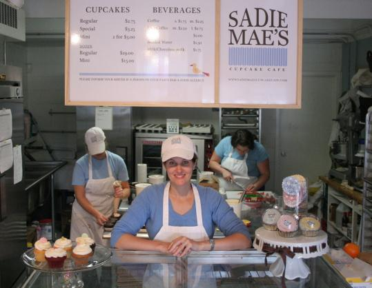 Sarah D'Souza at the counter of her shop, where customers can see into the kitchen. Each cupcake has a telltale topper, such as a peppermint stick or lemon rind.