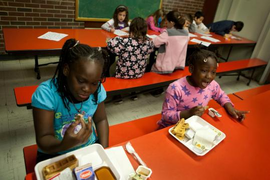 At Oaklandvale Elementary School in Saugus, Majesty Jackson, 10 (left), and Cleopatra Charlot, 6, eat breakfast before school starts.