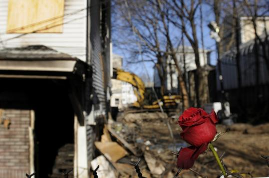 A rose was wrapped into the fence at the back of the burned three-decker in Worcester where firefighter Jon D. Davies Sr. died.