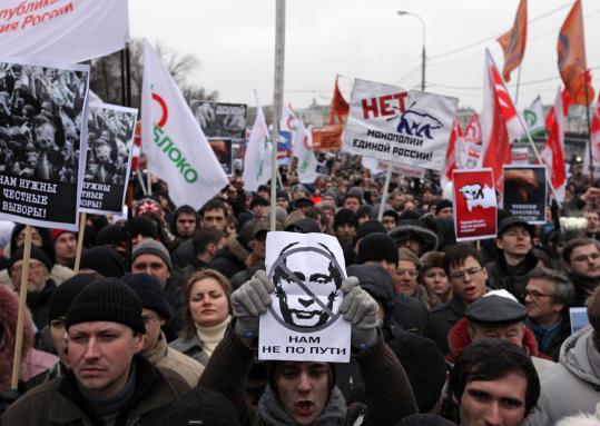 "Protesters in Moscow Saturday waved an image of Vladimir Putin and signs reading, ""We are going different ways."""