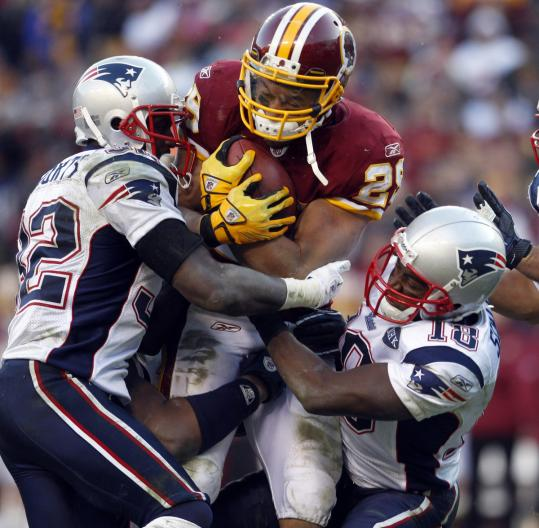 Redskins running back Roy Helu, who had a big day against a Patriots defense that showed signs of improvement, is stopped by the teamwork of Devin McCourty (left) and Matthew Slater.