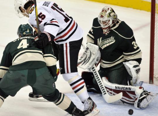 Wild goalie Niklas Backstrom stops the puck off the skate of Chicago's Andrew Brunette.
