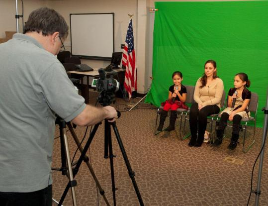 Walt Laskos adjusts the camera as Tiffany Hagler and her two daughters, Kaylie and Madison, prepare to tape a greeting for her husband, who is in Afghanistan.