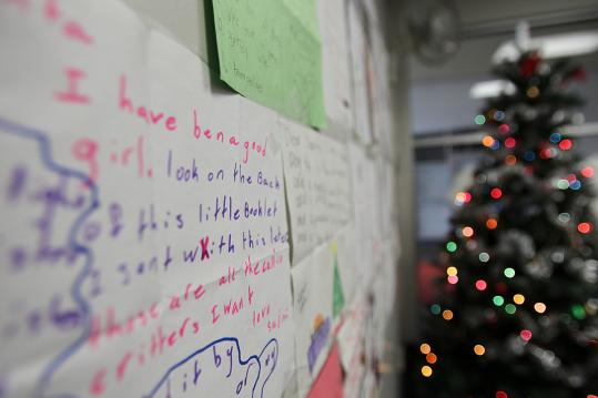 Some of the 1,200 children's letters to Santa Claus are posted on the Boston office walls of the US Postal Service as part of Operation Santa.