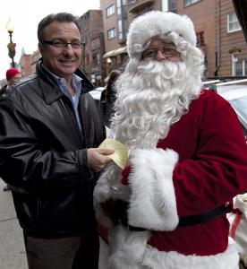 Councilor Salvatore LaMattina, who as a child received gifts from Globe Santa, presented his jolly friend with a $250 donation during a fund-raiser on Hanover Street Saturday.