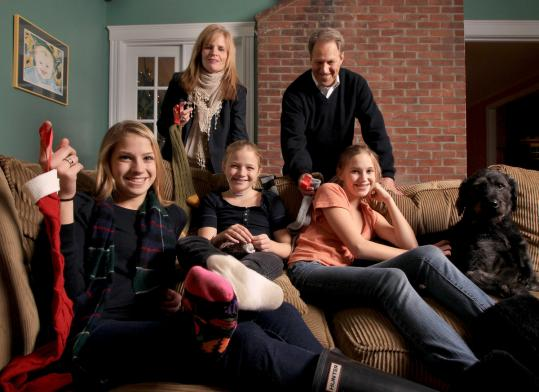 """The Kiefer family (from left): McKenna, 17, Rosie, 10, and Emma, 14, with their parents, Karen and Sam, and their Labradoodle, Keibo. In their Wayland home, they've hung socks of gratitude. A family tradition inspired Karen to write """"The Misfit Sock.''"""