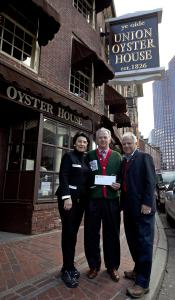 Mary Ann Milano-Picardi (left) and Joe Milano (right) gave their donation to Globe Santa's William Connolly.