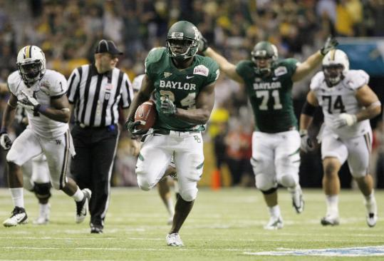 Baylor's Terrance Ganaway, center, upstaged Heisman Trophy winner Robert Griffin III in the highest-scoring bowl game ever. Ganaway rushed for 200 yards and five touchdowns.