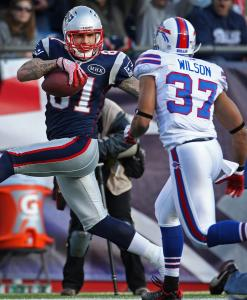 Aaron Hernandez strikes a pose just for the Bills' George Wilson as he strides untouched into the end zone in the second quarter.