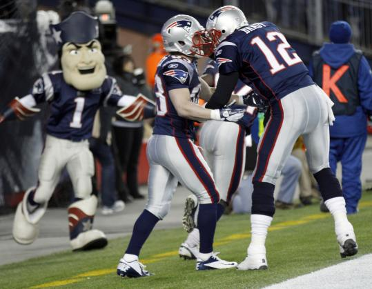 With an eager Pat Patriot ready to join in, Tom Brady and Wes Welker celebrate a New England touchdown Saturday.