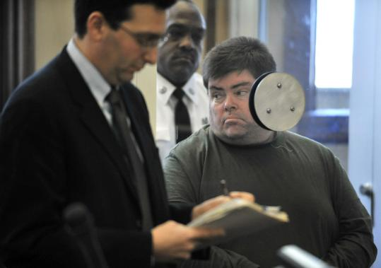 Peter Buchanan, 47, a Newton public library employee, with his lawyer, David Levinson, was arraigned in Newton District Court yesterday on charges of possession and distribution of child pornography.