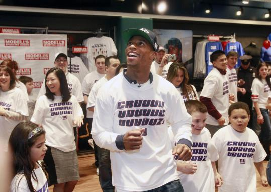Victor Cruz, who does the salsa after TD catches, dances with fans recently at a sporting goods store in New York.