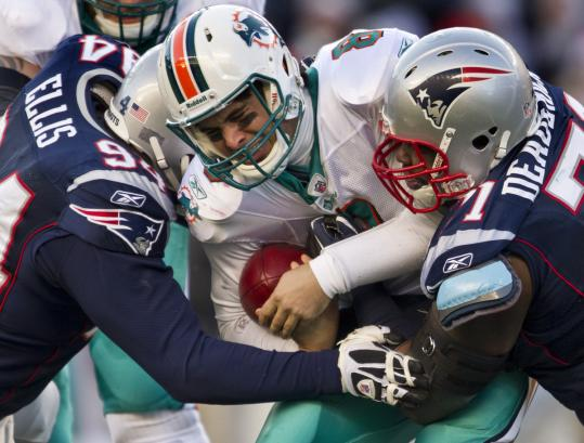 Shaun Ellis and Brandon Deaderick combine to take down Miami's Matt Moore for one of the Patriots' 51 sacks.