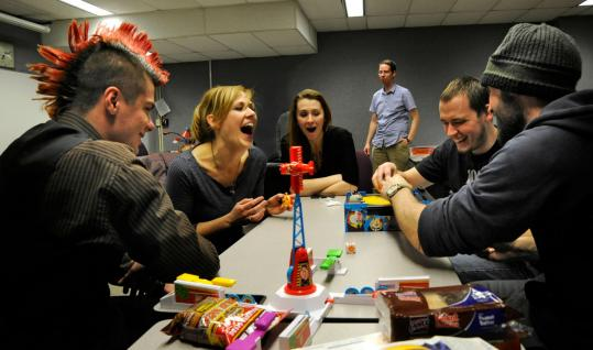 As professor Mike Cross looks on, (from left) Brady Tatro, Angela Bowie, Abby LaBonte, David Bowie, and Steven Edwards play a board game at Haverhill's Northern Essex Community College.