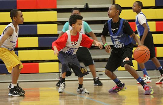 Charlie Mitchell, 14, tries to dribble past 10-year-old Merquiceeds Soto during the Basketball for Peace Tournament, which is run by Suffolk County District Attorney Daniel F. Conley.
