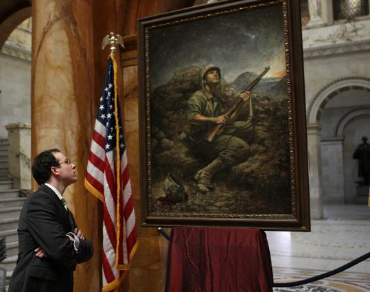 """Hopkinton artist Dustin Neece looks over his painting """"Honoring the Spirit,'' on display at the State House for Iwo Jima Day."""