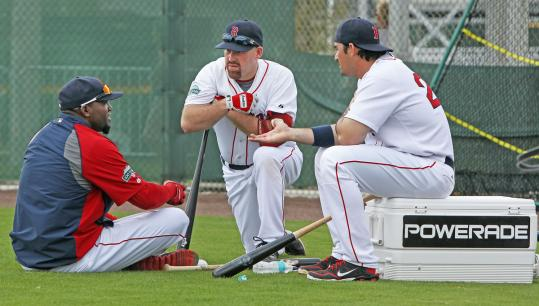 David Ortiz (left), Kevin Youkilis, and Adrian Gonzalez chat. Gonzalez sits on a cooler of Powerade, maybe a clubhouse refreshment of choice of the Sox this season with alcohol banned.