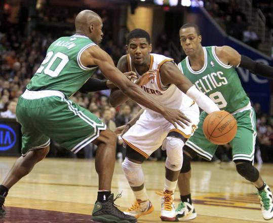 The Cavaliers' Kyrie Irving splits Celtics Ray Allen (20) and Rajon Rondo at the top of the key during the second quarter.