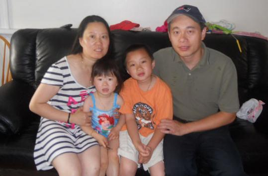 Marshfield restaurant owner Kong Xin Chen (right) with his wife, Ping, and children, Grace and Jason.